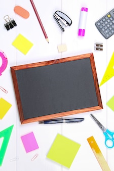 Chalkboard surrounded by stationery on white wooden table. copy the space.