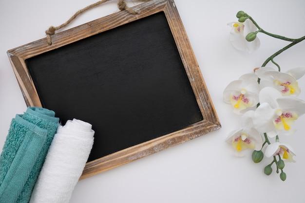 Lavagna, asciugamani e fiori
