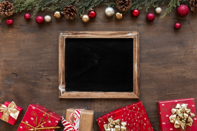 Chalkboard with bright gift boxes on table