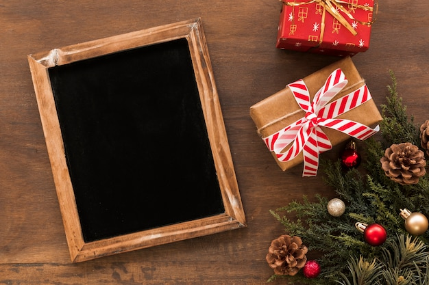Chalkboard with christmas gift boxes on table