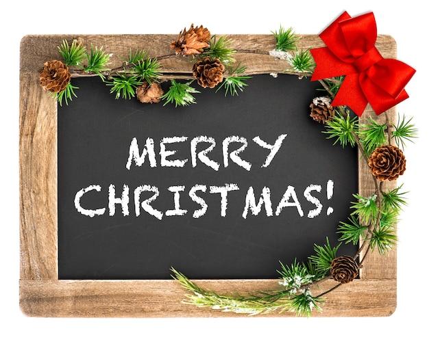 クリスマス飾りと赤いリボンの弓が付いている黒板。メリークリスマス!
