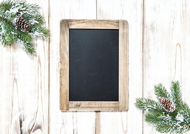 明るい木製の背景にクリスマスツリーの枝の装飾と黒板