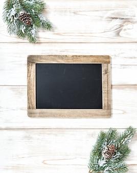 木製の壁の背景にクリスマスツリーの枝の装飾と黒板