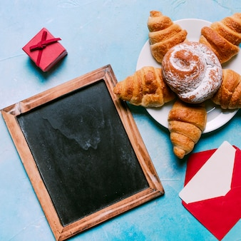 Chalkboard with croissants and bun on plate