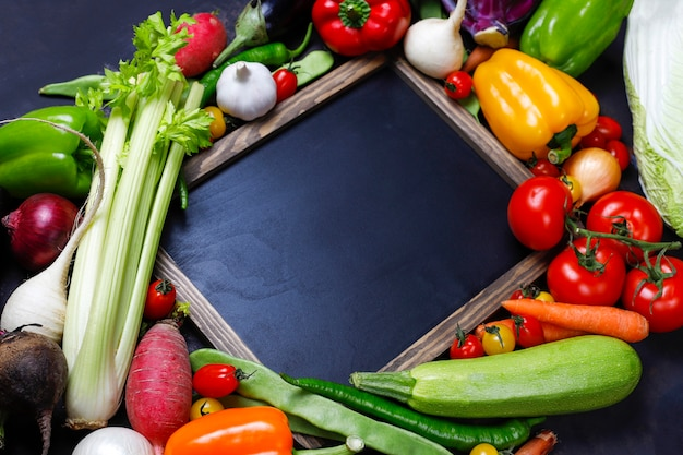 Chalkboard with different colorful healthy vegetables on dark background