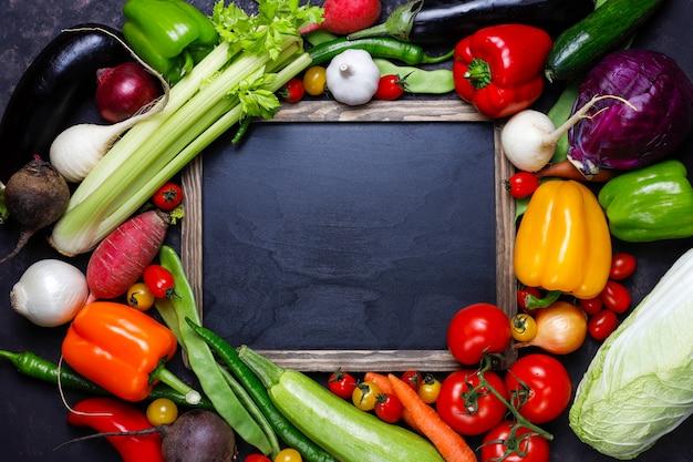 暗い背景にさまざまなカラフルな野菜と黒板