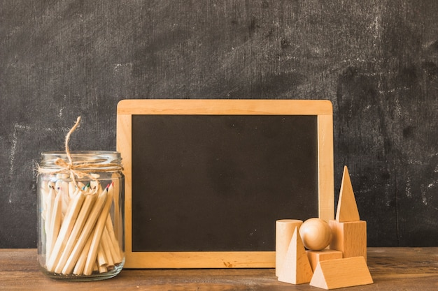Chalkboard with drawing pens and wooden shapes