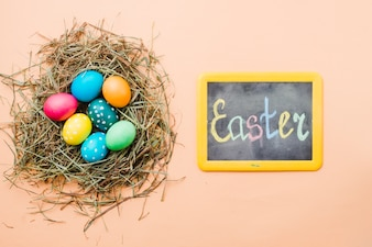 Chalkboard with Easter title near set of bright colored eggs in nest