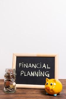 財務計画テキストと貯金箱のある黒板