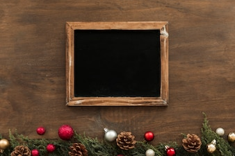 Chalkboard with green branches on table