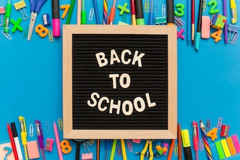Chalkboard with group of school supplies on a blue background.