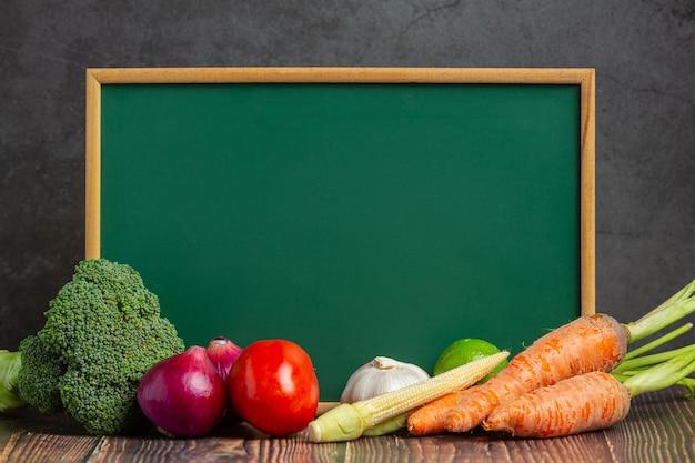 古い暗い背景の上の健康野菜と黒板