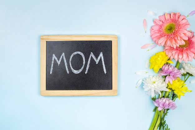 Chalkboard with mom title near bunch of fresh bright flowers