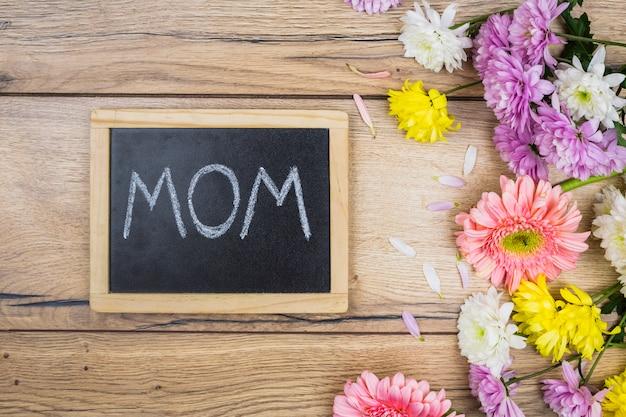 机の上の新鮮な明るい花の近くのお母さんのタイトルと黒板