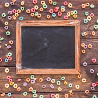 Chalkboard with scattered cereals on table