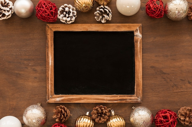 Chalkboard with shiny baubles on table