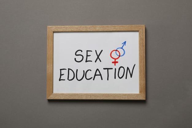 灰色の壁にテキストの性教育と黒板