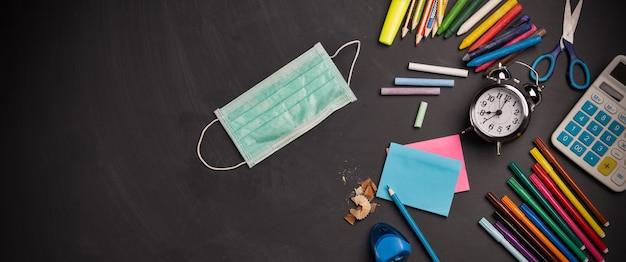 칠판과 의료용 마스크 학용품 위에 학용품이 있는 칠판