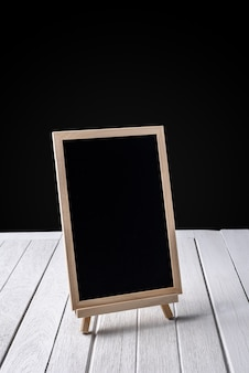 The chalkboard on wooden floor and black background