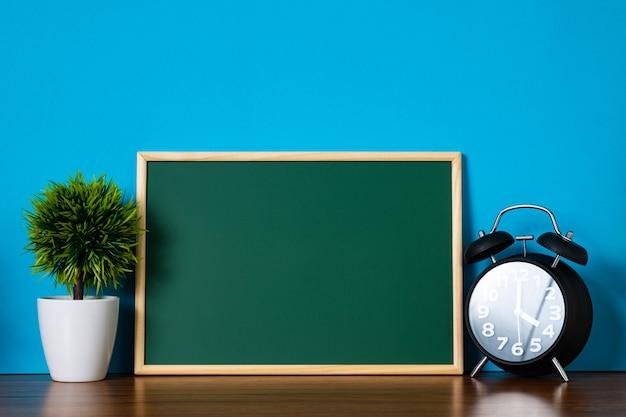 空白の緑chalkboradと小さな装飾ツリーとビンテージ目覚まし時計