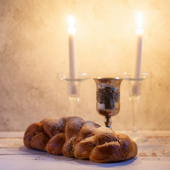 Challah bread, shabbat wine and candles on wooden table