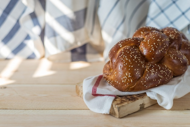 Challah bread or traditional jewish bread on a wood plate on wooden table