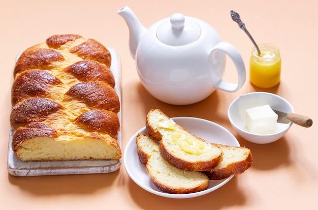 밝은 오렌지색 배경에 찻주전자와 빵이 있는 효모 반죽으로 만든 할라