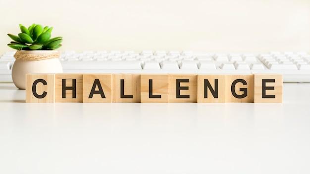 木製のブロックで作られたチャレンジワード。正面図の概念、花瓶の緑の植物と背景の白いキーボード