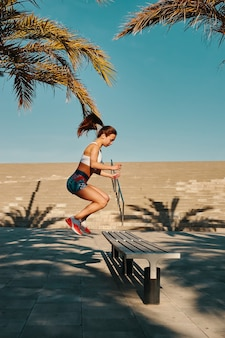 自分自身に挑戦します。屋外で運動しながらジャンプするスポーツウェアの美しい若い女性の全長