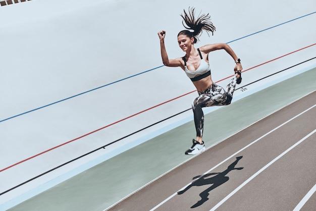 Бросая вызов себе. вид сверху молодой женщины в спортивной одежде прыгает и улыбается