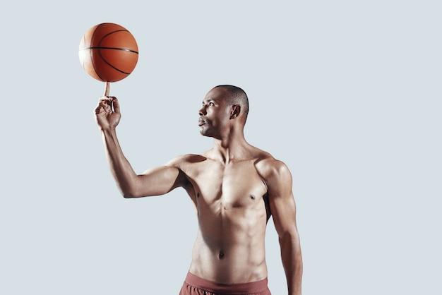自分自身に挑戦します。灰色の背景に立っている間、指でボールを回転するハンサムな上半身裸のアフリカ人