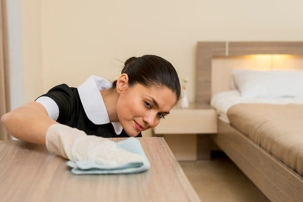 Chambermaid cleaning hotel room
