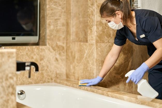 Горничная делает дезинфекцию специальными средствами в ванной