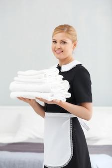 Горничная держит стопку чистых полотенец в комнате