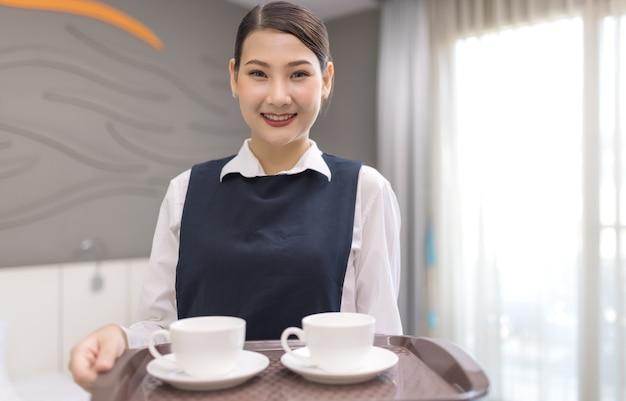 Горничная держит поднос с чашкой кофе
