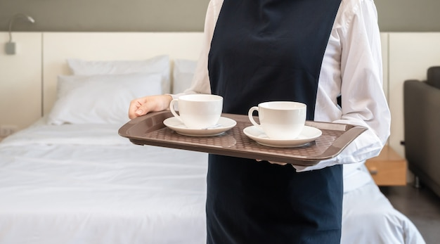 Chambermaid holding tray with cups of coffee.  hotel room service concept.
