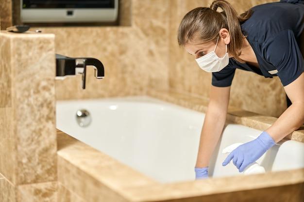 Горничная в маске наклоняется в ванную и умывается
