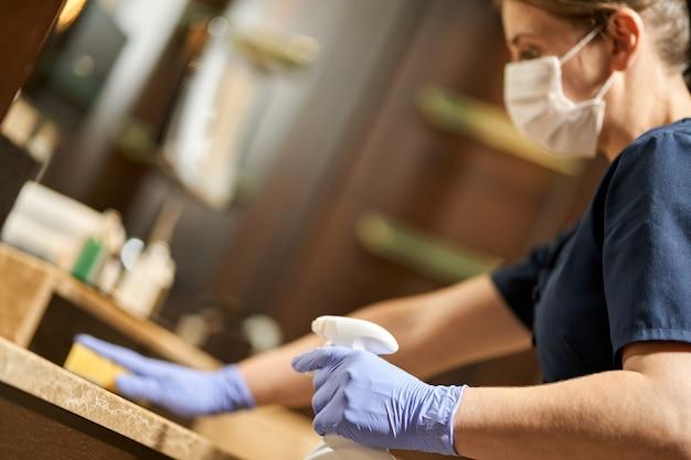 Горничная в защитных перчатках делает дезинфекцию поверхностей в ванной комнате