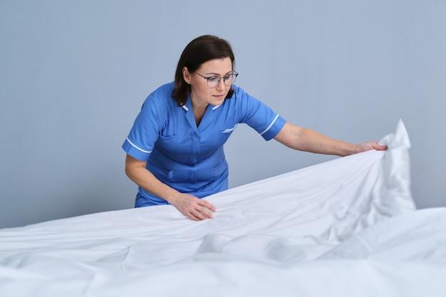 호텔 침실에서 손님 침대를 만드는 하녀. 서비스, 청소, 직원, 호텔 컨셉