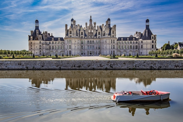 Chambord castle with some people boating on the canal that surrounds it