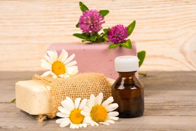 Мыло ручной работы с ромашкой и клевером и эфирным маслом в бутылочке