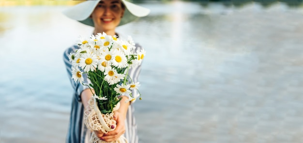 Chamomile bouquet in girl's hands on river.
