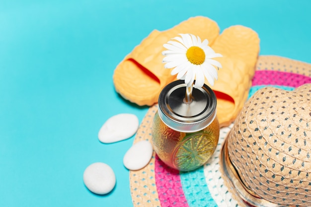 Chamomile flower in straw of juice glass mug, woman summer hat, yellow slippers white smooth pebbles