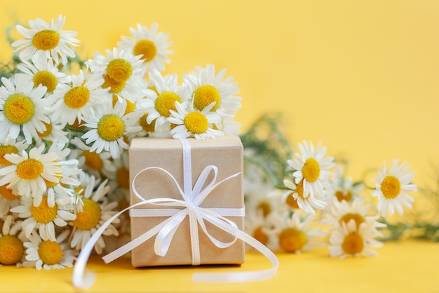 Chamomile flowers and gift or present box on yellow