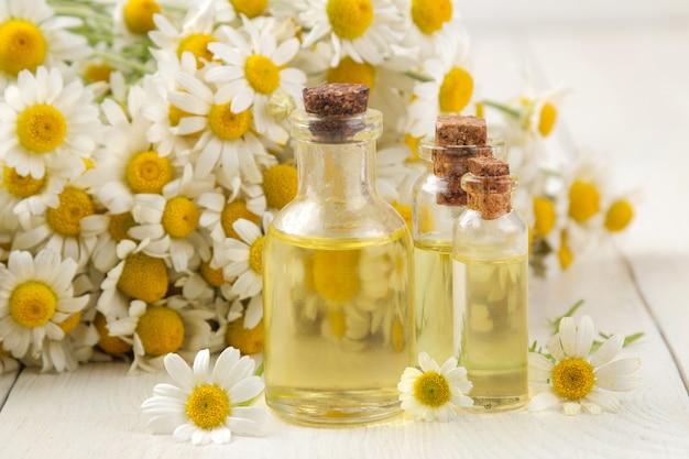 Ромашка. лекарственные цветки ромашки с ароматическими маслами на белом деревянном столе. крупный план