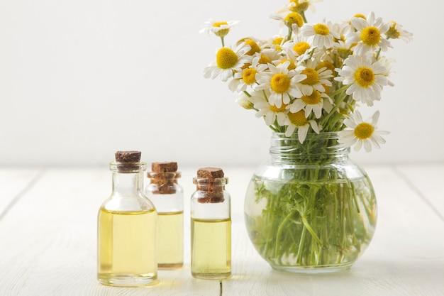 카밀레. 흰색 나무 테이블에 아로마 오일이 있는 카모마일의 약용 작은 꽃. 텍스트를 위한 공간