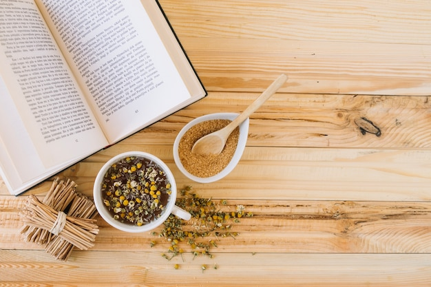 Chamomile tea and brown sugar near book