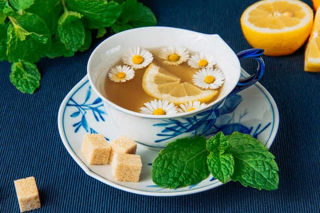 Chamomile tea in a cup and lemon slices, brown sugar cubes and green leaves side view on a dark placemat background