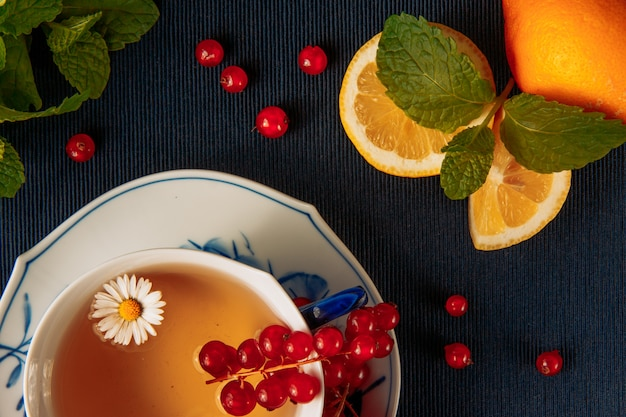 Chamomile tea in cup and sauce with lemon, scattered red currant berries and green leaves on dark blue placemat background. vertical. high angle view