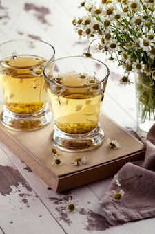 Chamomile tea cups on wooden board